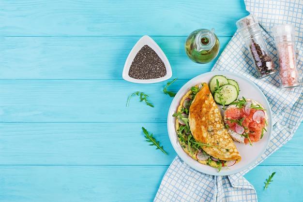 Omelet met radijs, groene rucola en sandwich met zalm op witte plaat Premium Foto