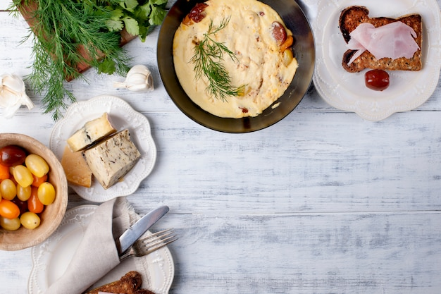 Omelet met tomaat in een koekenpan voor ontbijt, kaas en greens op een witte houten achtergrond Premium Foto