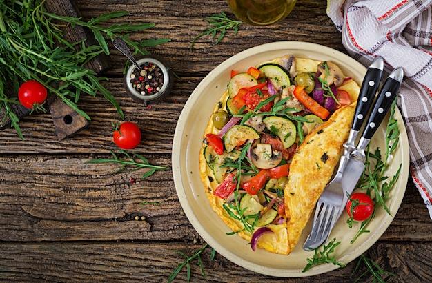 Omelet met tomaten, courgette en champignons. omelet ontbijt. gezond eten. bovenaanzicht plat leggen Premium Foto