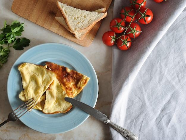 Omelet op een bord, peterselie, tomaten, toast Premium Foto