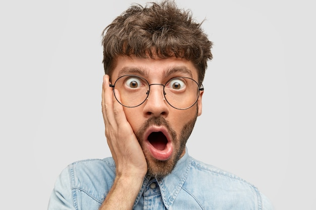 Omg, wat ik deed! verrast bange jonge man met stoppels raakt wang en opent mond, geschokt Gratis Foto
