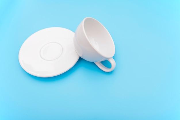 Omgedraaid of omvergegooid lege witte koffiekop, mok met kom Premium Foto