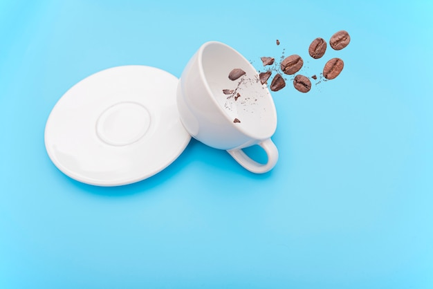 Omgedraaid of omvergeworpen witte koffiekop, mok met kom en koffiebonen Premium Foto