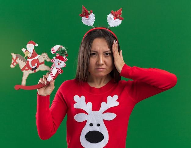 Onaangenaam jong aziatisch meisje die de hoepel van het kerstmishaar met sweater dragen die kerstmisstuk speelgoed met suikergoed houden die hand op hoofd zetten dat op groene achtergrond wordt geïsoleerd Gratis Foto