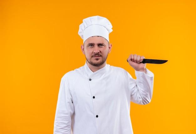 Onaangename jonge knappe kok in mes van de chef-kok het eenvormige bedrijf dat op oranje ruimte wordt geïsoleerd Gratis Foto
