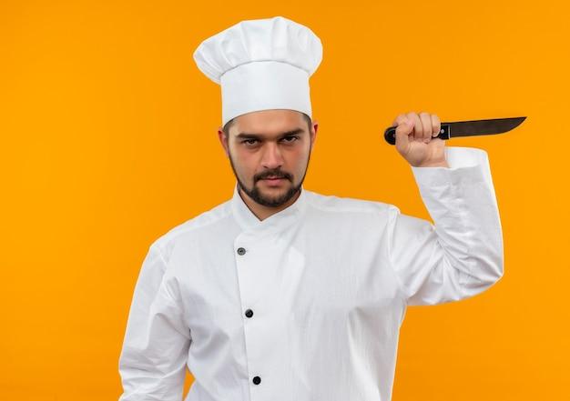 Onaangename jonge mannelijke kok in mes van de chef-kok het eenvormige bedrijf dat op oranje ruimte wordt geïsoleerd Gratis Foto
