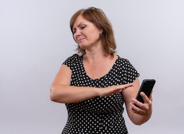 Onbehaagde vrouw van middelbare leeftijd die mobiele telefoon houdt en met de hand erop wijst op geïsoleerde witte achtergrond Gratis Foto