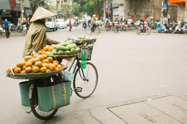 Onbekende man rijdt op een fiets met manden in hanoi, vietnam. straatverkoop per fiets is een essentieel onderdeel van het leven in vietnam Premium Foto