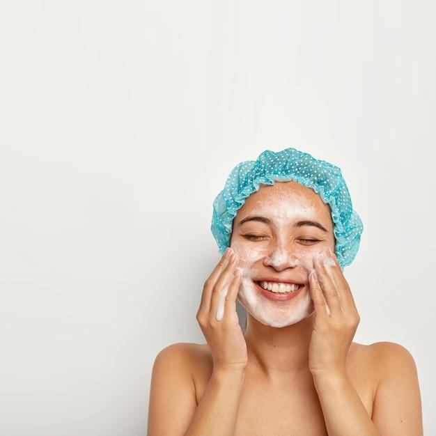 Onberispelijke en zuiverheid van de huid. verticale afbeelding van mooie vrouw wast gezicht, geniet van koud water, heeft schuim op de huid, glimlacht vreugdevol, houdt de ogen gesloten, zorgt voor persoonlijke hygiëne. wellness-concept Gratis Foto