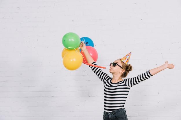 Onbezorgde tiener die kleurrijke ballons houden die deelhoorn blazen die zich tegen muur bevinden Gratis Foto