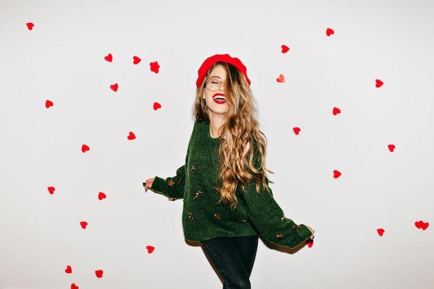 Onbezorgde vrouw met krullend lichtbruin haar lachend met gesloten ogen in valentijnsdag Gratis Foto