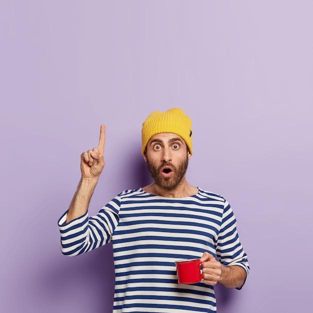 Onder de indruk duizendjarige man wijst met wijsvinger naar boven, heeft een geschokte uitdrukking, drinkt 's ochtends koffie, houdt een rode mok vast, draagt een gele hoed en een gestreepte zeemanstrui, laat iets zien Gratis Foto