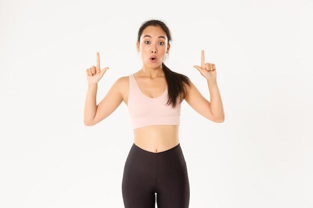 Onder de indruk en nieuwsgierige aziatische vrouwelijke atleet zegt wow, kijkt verbaasd en wijst met de vingers omhoog, wil details over kortingen en speciale aanbiedingen weten. Premium Foto
