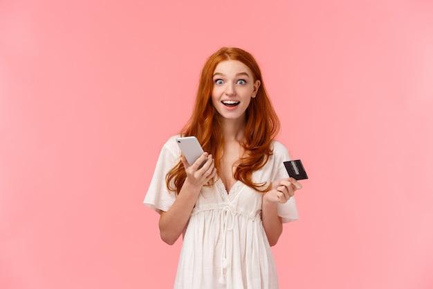 Onder de indruk en opgewonden, gelukkig roodharige meisje in witte jurk, verbaasd over hoe gemakkelijk ze een aankoop deed Premium Foto