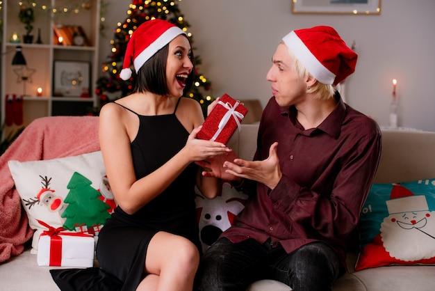 Onder de indruk jong koppel thuis kerst tijd dragen kerstmuts zittend op de bank in de woonkamer geschenken ontvangen Gratis Foto