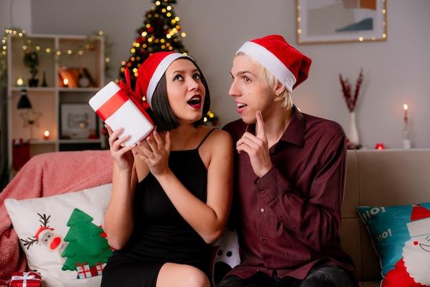 Onder de indruk jong koppel thuis kerst tijd dragen kerstmuts zittend op de bank in de woonkamer Gratis Foto