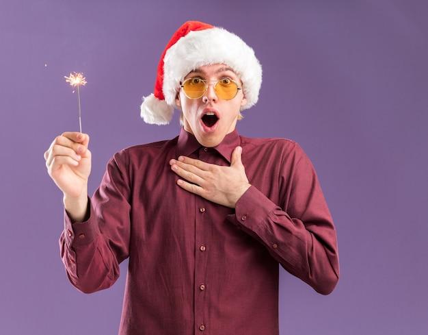 Onder de indruk jonge blonde man met kerstmuts en bril met vakantie sterretje kijken camera houden hand op borst geïsoleerd op paarse achtergrond Gratis Foto