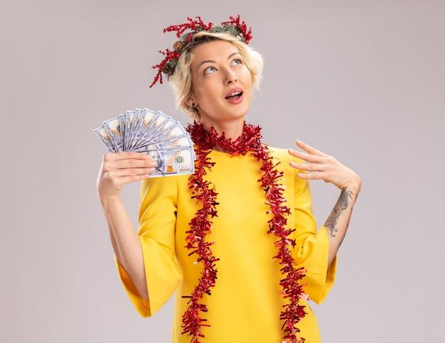 Onder de indruk jonge blonde vrouw die de hoofdkrans van kerstmis en een klatergoudslinger om de hals draagt die geld houdt hand in de lucht houdt die omhoog kijkt geïsoleerd op witte muur Gratis Foto