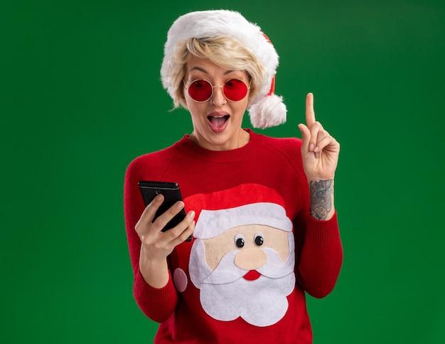 Onder de indruk jonge blonde vrouw met kerstmuts en kerstman kerst trui met bril houden en kijken naar mobiele telefoon omhoog geïsoleerd op groene muur met kopie ruimte Gratis Foto