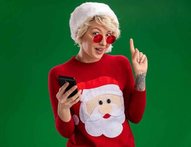 Onder de indruk jonge blonde vrouw met kerstmuts en kerstman kerst trui met bril houden mobiele telefoon kijken en omhoog geïsoleerd op groene muur met kopie ruimte Gratis Foto