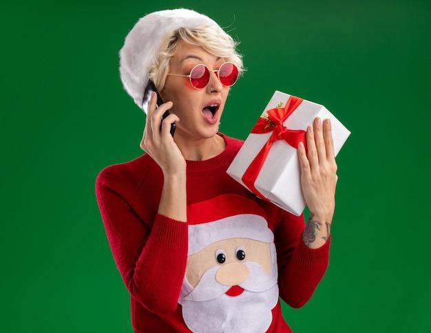 Onder de indruk jonge blonde vrouw met kerstmuts en kerstman kersttrui met bril houden en kijken naar geschenkpakket praten aan de telefoon geïsoleerd op groene muur Gratis Foto