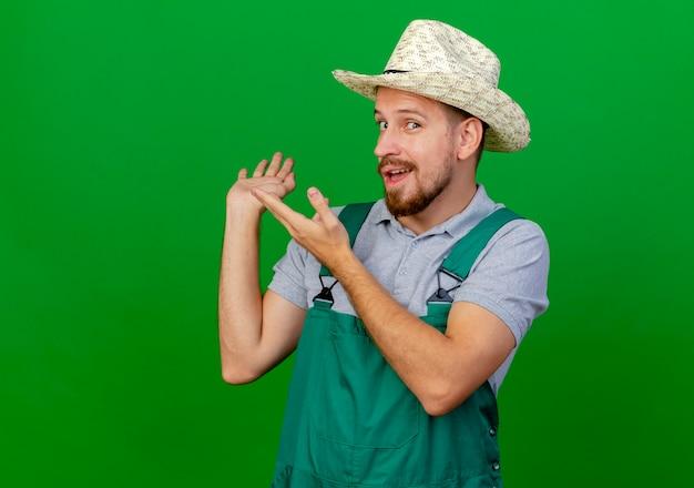 Onder de indruk jonge knappe slavische tuinman in uniform en hoed op zoek wijzend met handen erachter Gratis Foto