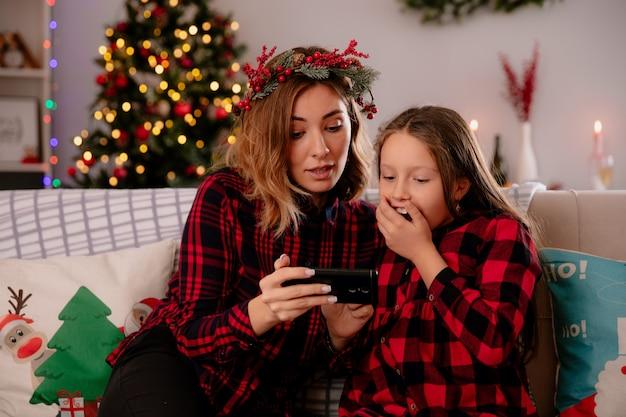 Onder de indruk moeder en dochter kijken naar iets op telefoon zittend op de bank en genieten van kersttijd thuis Gratis Foto