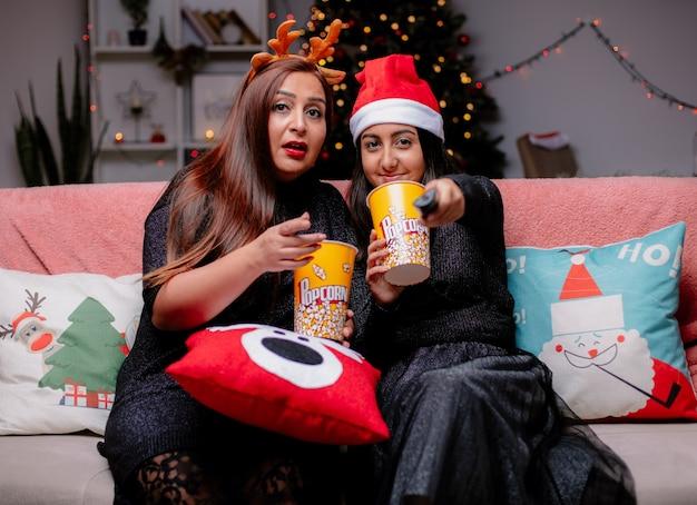 Onder de indruk moeder houdt popcorn emmer wijzend op camera en tevreden dochter met kerstmuts houdt tv afstandsbediening zittend op de bank genieten van kersttijd thuis Gratis Foto