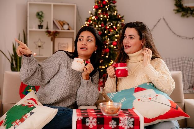Onder de indruk mooie jonge meisjes houden bekers vast en kijken naar de zijkant zittend op fauteuils en genieten van kersttijd thuis Gratis Foto
