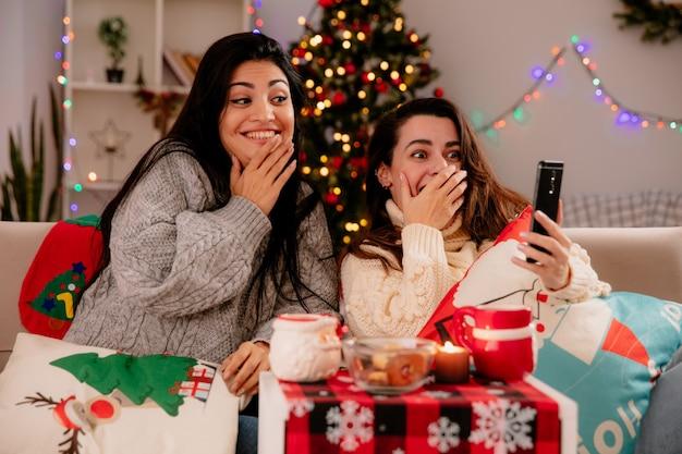 Onder de indruk mooie jonge meisjes kijken naar telefoon zittend op fauteuils en genieten van kersttijd thuis Gratis Foto