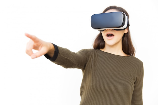 Onder de indruk opgewonden vrouw in vr-headset wijzende vinger weg Gratis Foto
