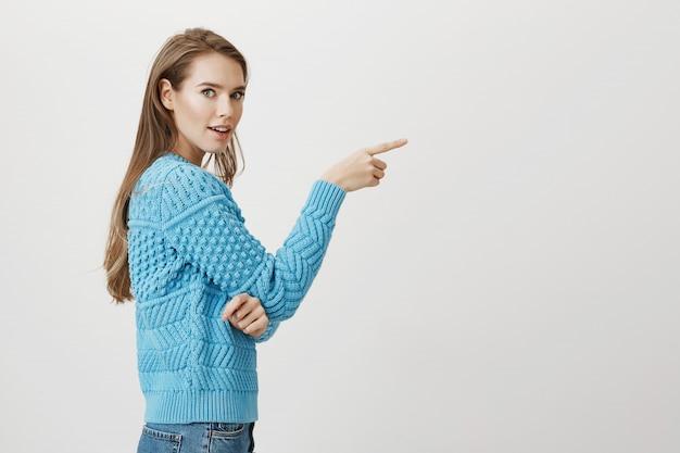 Onder de indruk vrouw draai naar camera en wijzende vinger naar rechts Gratis Foto