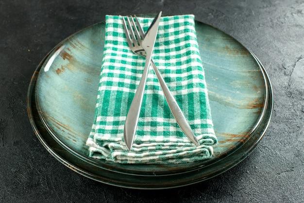 Onderaanzicht gekruist diner mes en vork op groen en wit geruit servet op schalen op zwarte tafel Gratis Foto