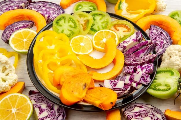 Onderaanzicht gesneden groenten en fruit gele paprika pompoen persimmon rode kool citroen groene tomaten op schotel op tafel Gratis Foto