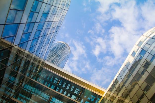 Onderaanzicht van de glazen wolkenkrabbers van het zakelijke district van la defense van parijs tegen een blauwe bewolkte hemel Premium Foto