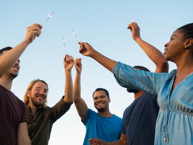 Onderaanzicht van gelukkige mensen die zich met bengalen lichten bevinden. glimlachende vrienden die tijd samen doorbrengen openlucht. concept van viering Gratis Foto
