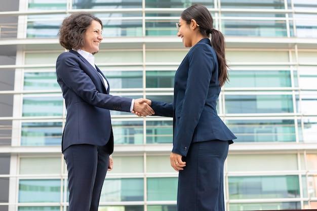 Onderaanzicht van vrolijke collega's handen schudden in de buurt van gebouw. jonge vrouwen die formele kostuums openlucht samenkomen dragen. handdruk bedrijfsconcept Gratis Foto