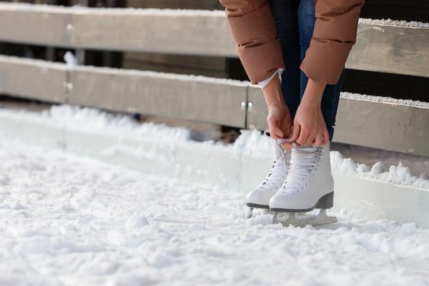 Onderaanzicht van vrouwelijke veters strikken / witte schaatsen dragen op ijsbaan in de winterdag. weekendactiviteiten buiten bij koud weer Premium Foto