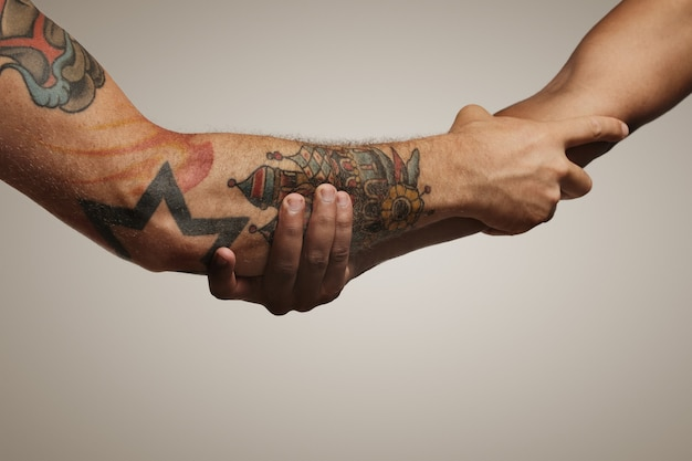 Onderarm schudden van twee jonge mannelijke vrienden geïsoleerd op wit Gratis Foto