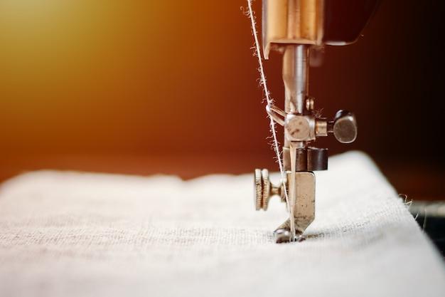 Onderdeel van een vintage naaimachine en kledingstuk. stalen naald met grijper en naaivoetclose-up. Premium Foto