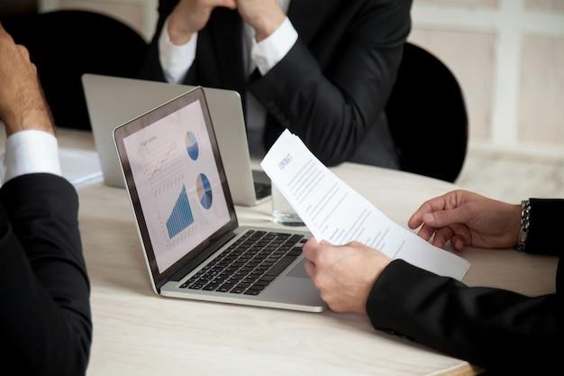 Onderhandelingen op contract tijdens vergadering van drie partners, close up Gratis Foto
