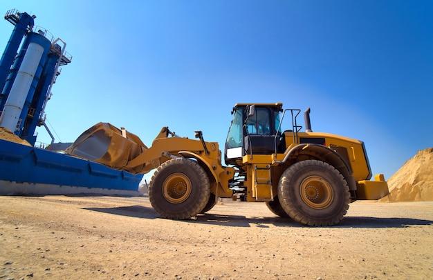 Onderhoud van gele graafmachine op een bouwplaats tegen blauwe hemel Premium Foto