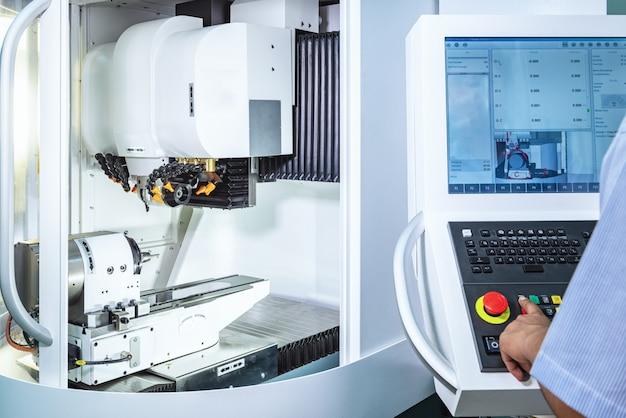 Onderhoudsingenieur die industrieel robotachtig holdings automobieldeel met cnc machine controleren Premium Foto