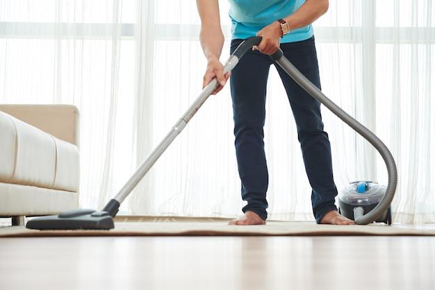 Onderlichaam schot van onherkenbaar mensen stofzuigend tapijt thuis Gratis Foto
