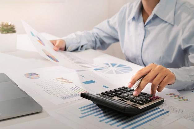Onderneemster die aan bureau werkt die calculator en laptop met behulp van die financiënboekhouding in bureau analyseren Premium Foto