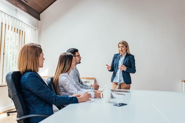 Onderneemster die aan collega's op een vergadering voorstellen. ruimte kopiëren. Premium Foto