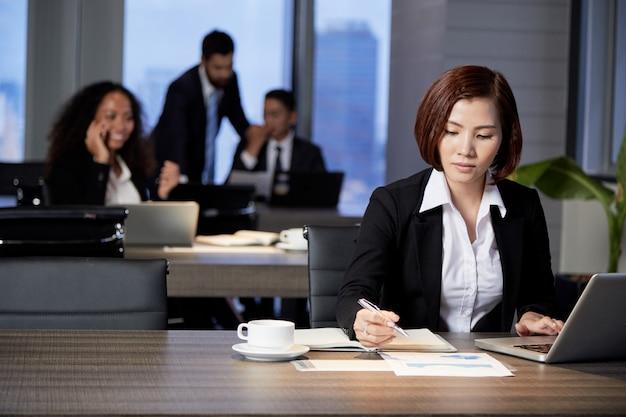 Onderneemster die met document in bureau werkt Gratis Foto