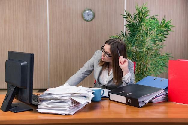 Onderneemster die onder spanning in het bureau werken Premium Foto