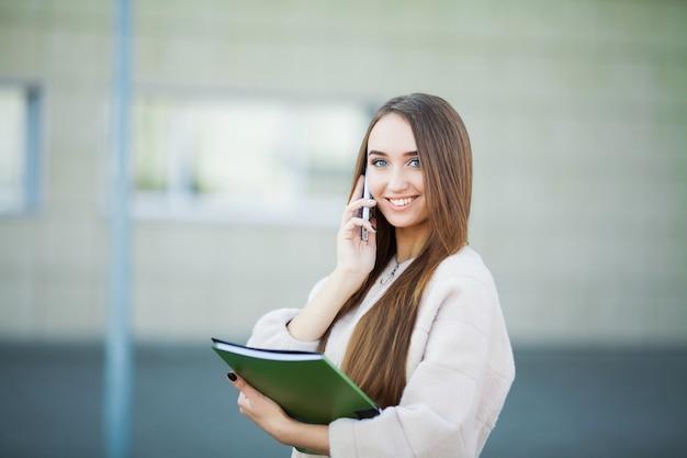 Onderneemster die op mobiele telefoon in cityscape lviv spreekt Premium Foto
