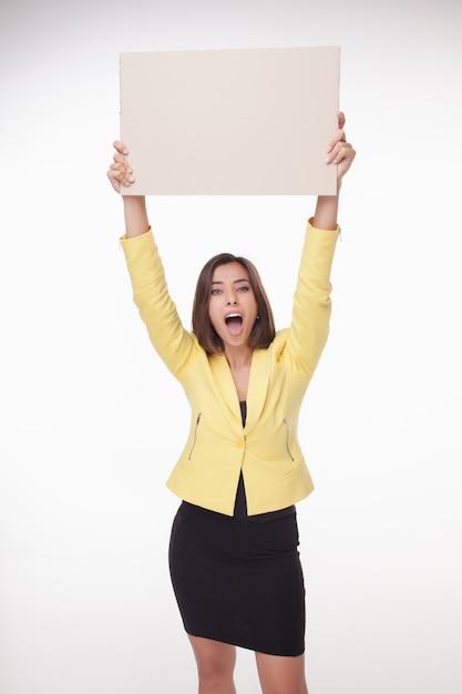 Onderneemster die raad of banner met exemplaarruimte toont op witte achtergrond Gratis Foto